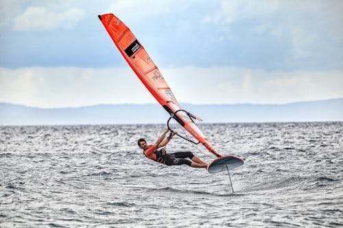 profesjonalny windsurfer łapie wiatr w żagiel i trenuje na otwartym morzu