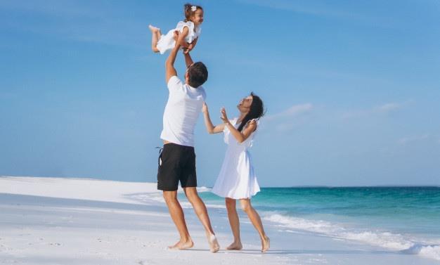 kobieta i mężczyzna stoją nad morzem i bawią się z dzieckiem