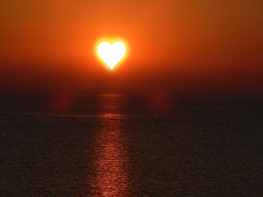 Zachód Słońca w kształcie serca nad morzem
