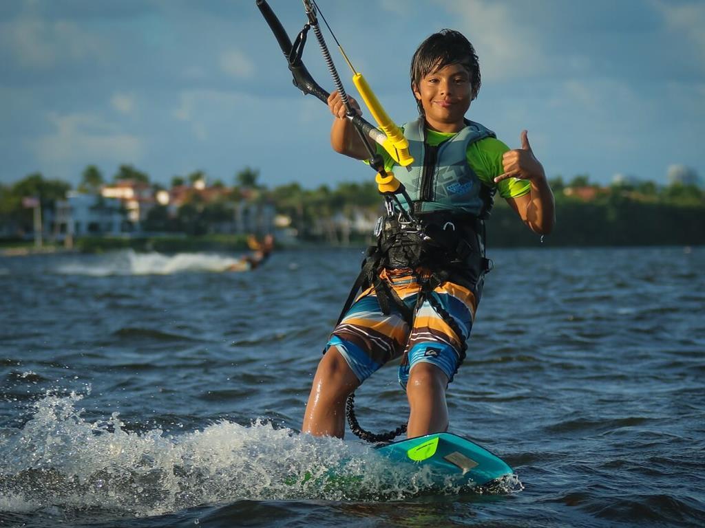 Uśmiechnięte dziecko pozujące podczas zabawy kitesurfingowej.