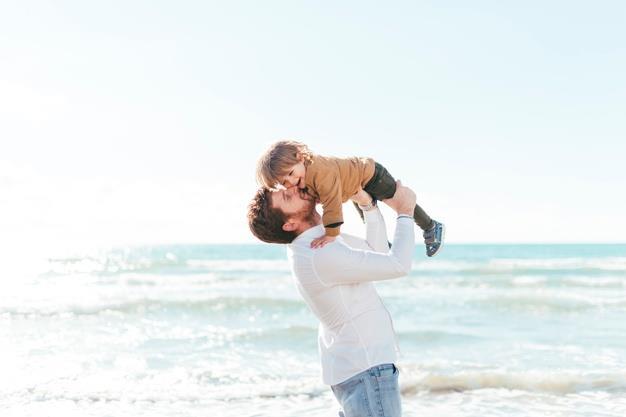 mężczyzna podnosi dziecko do góry nad morzem