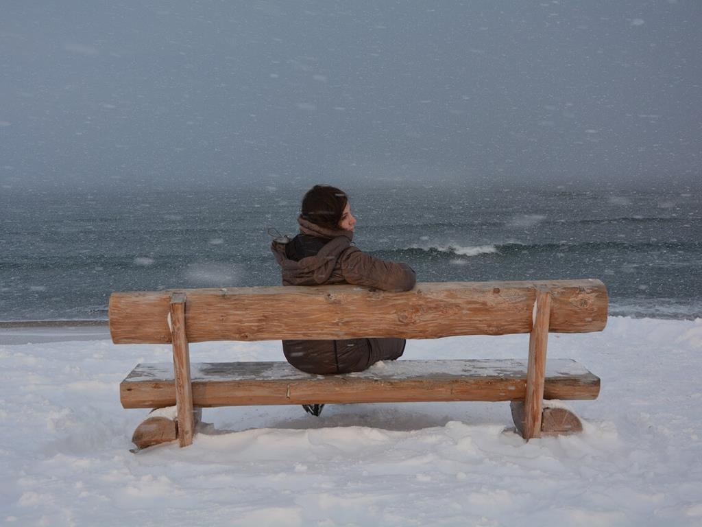 Kobieta przyglądająca się morzu w zimie