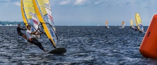 grupa mężczyzn trenuje windsurfing na morzu