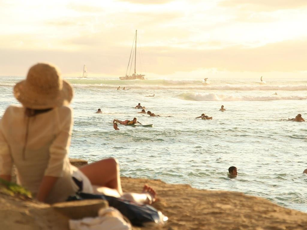 Kobieta odpoczywająca, gdy reszta jej rodziny kąpie się w morzu.