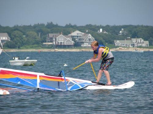 kobieta trenująca windsurfing podnosi żagiel z wody stojąc na desce