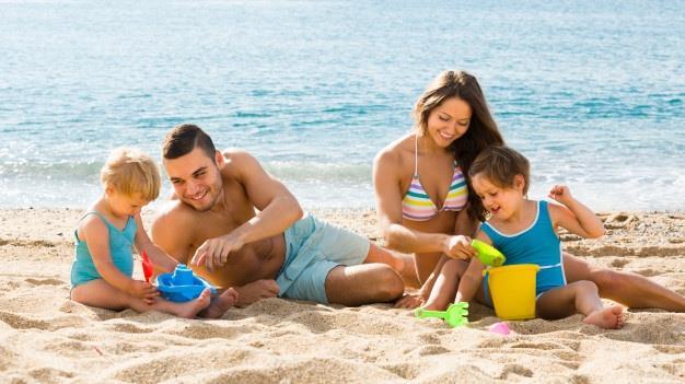 rodzina z dziećmi bawi się na plaży nad morzem